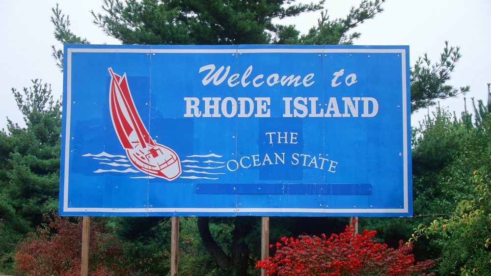 """blue road sign reads, """"Welcome to Rhode Island, the Ocean State."""""""