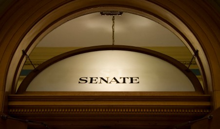 """A photograph of the word """"Senate"""" on glass above a door leading to the U.S. Senate"""