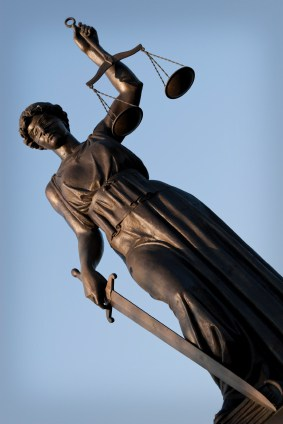 Photo of a bronze statute of lady justice holding a sword and scales.