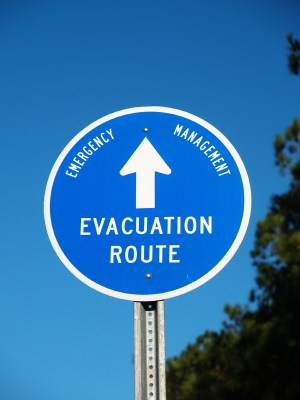 Photo of an evacuation route sign against a blue sky.