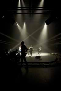 Black and white photo of the band Rudely Interrupted with spotlights shining down on them.