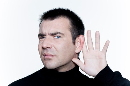 Photo of a man with a puzzled look on his face and his hand to his ear.