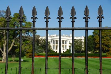 Photo of the White House through railings.