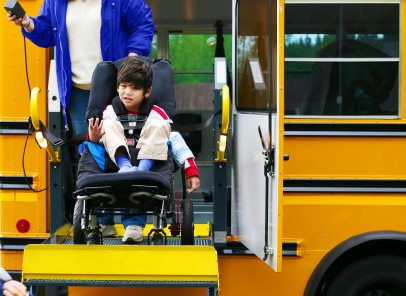 Photo of young boy in a wheelchair using the lift on a school bus.