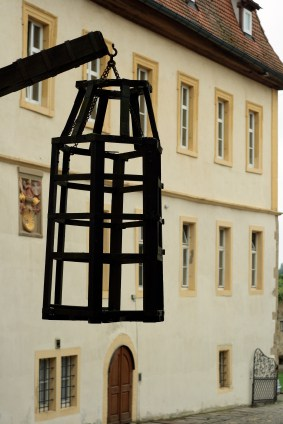 Photo of a cage of steel suspended in the air in front of an old building.