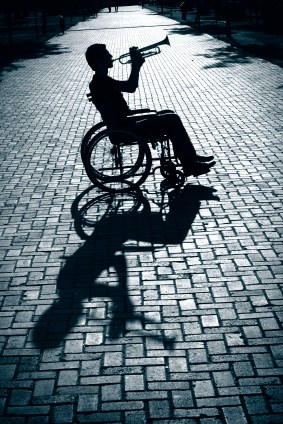 Black and white photo of a trumpet player in a cobblestone road using a wheelchair.