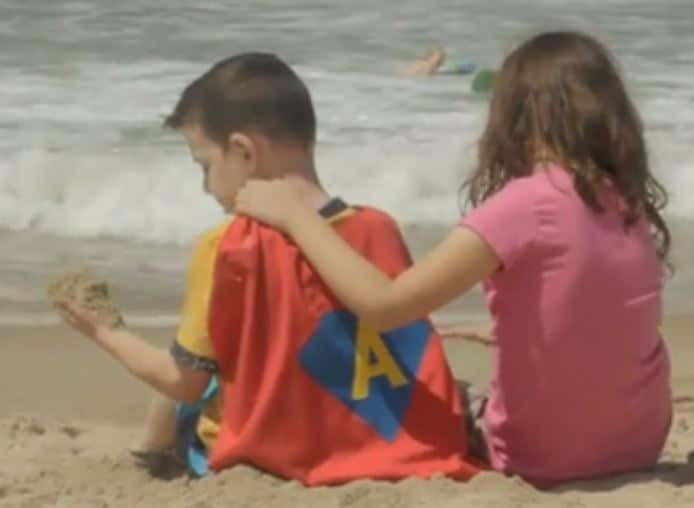 Two children sit on beach with backs toward camera, girl with her arm around boy who wears a superhero cape