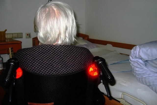 white haired woman in wheelchair in nursing home