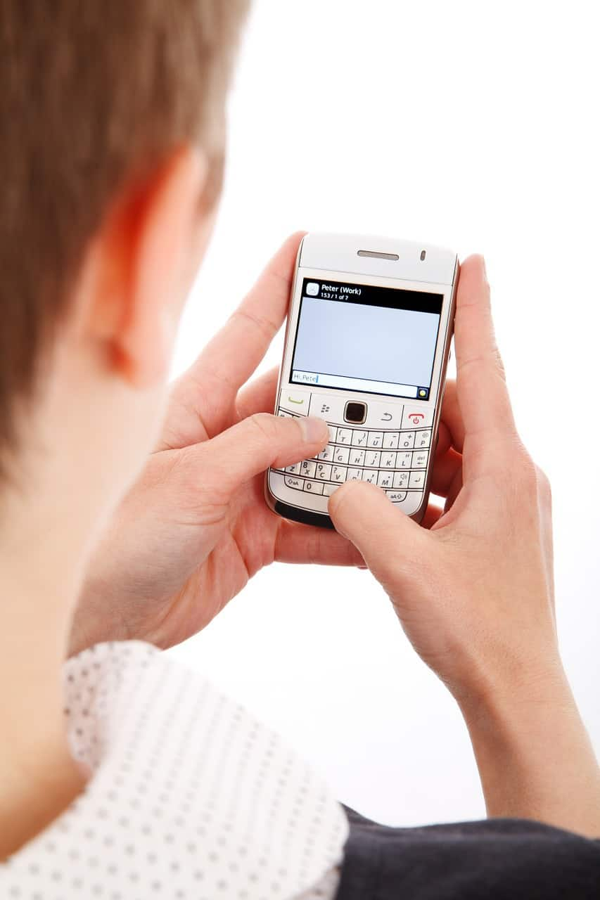 person texting on hand-held phone