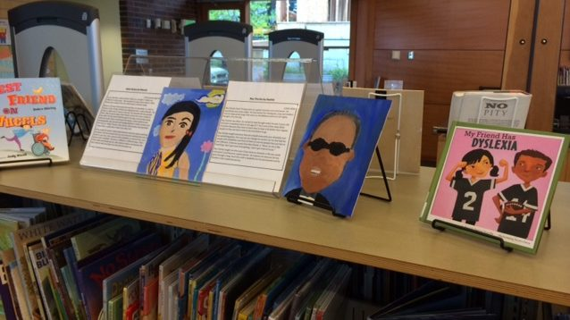 two portraits painted by children are displayed on a bookshelf, each next to a page of text