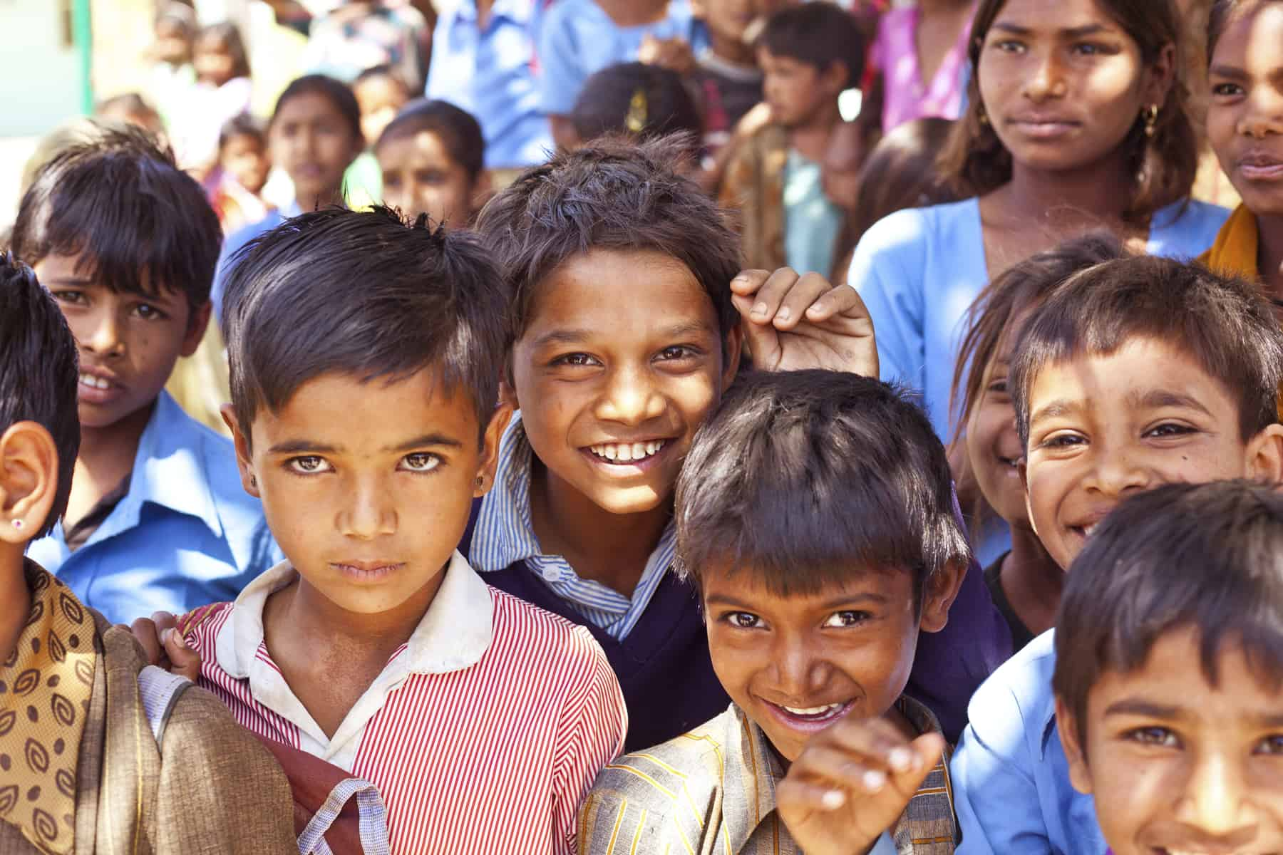 group of indian school children smiling at a camera