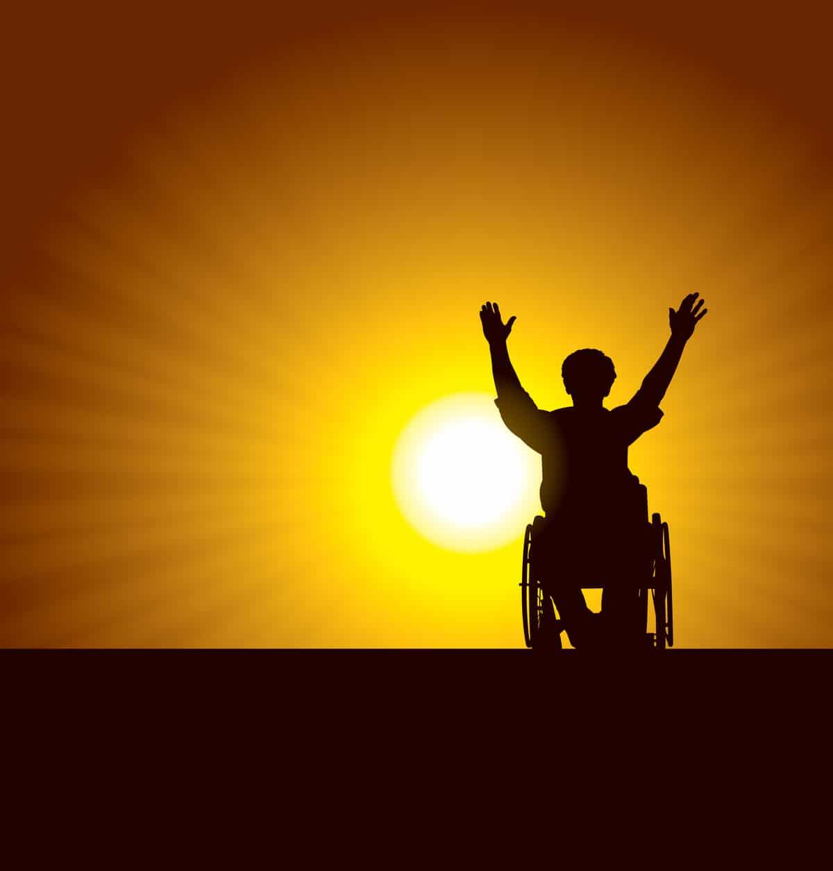 man in wheelchair arms raised against a setting sun