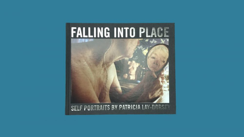 Book Cover: Falling into Place, Self Portraits by Patricia Lay-Dorsey, with self portrait of white-haried woman holding a mirror