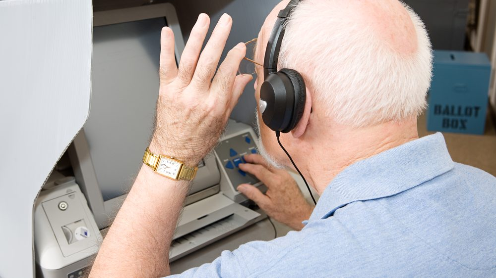 Senior man using headphones and voting on an accessible voting machine.