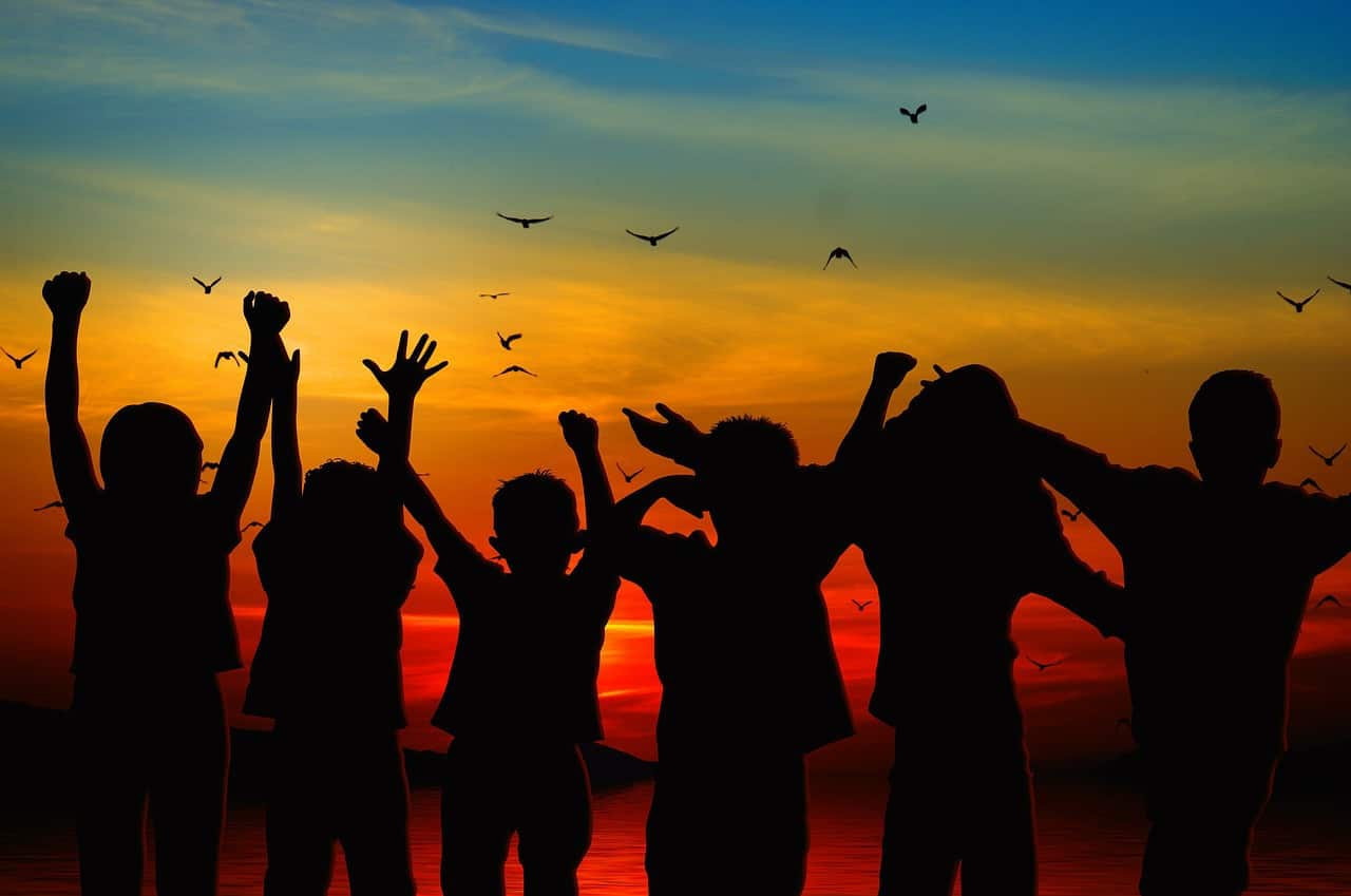 Children with arms raised in silhouette against a sunset colored sky