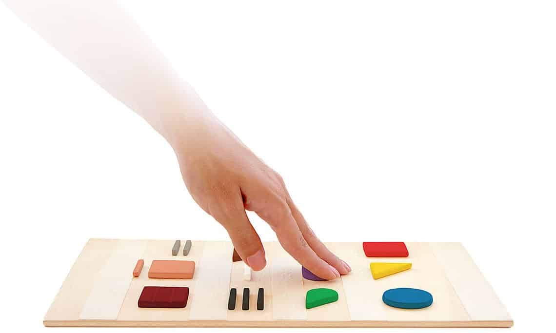 Hand touching a board of color code shapes