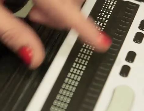 woman's fingers moving across a braille reader board