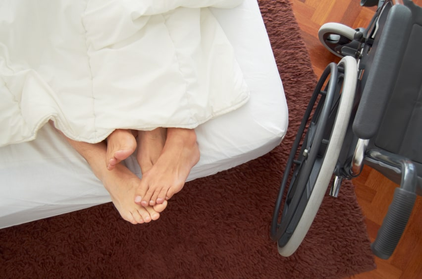 Image of a person with a disability in bed with partner