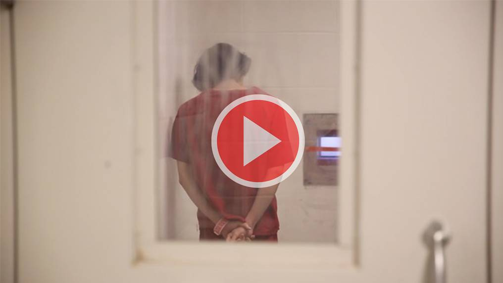 An inmate stands with hands cuffed behind him, with his back to the viewer, viewed through a blurry cell window