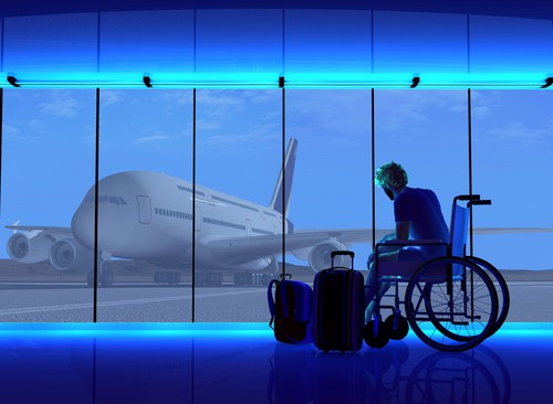 Man in wheelchair next to his baggage in an animated airport terminal, outside beyond a wall of windows, sits a plane on a tarmac