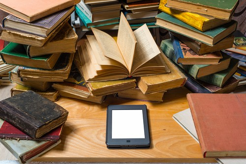 e-reader on a desk with a pile of books