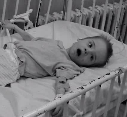 child lies in bed with chipped metal railings