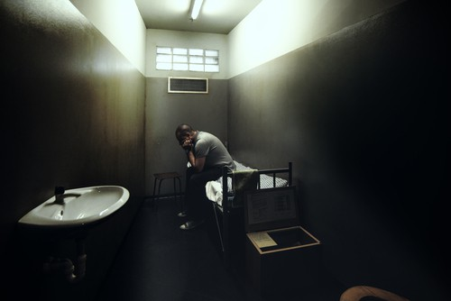 Man sits in cramped jail cell