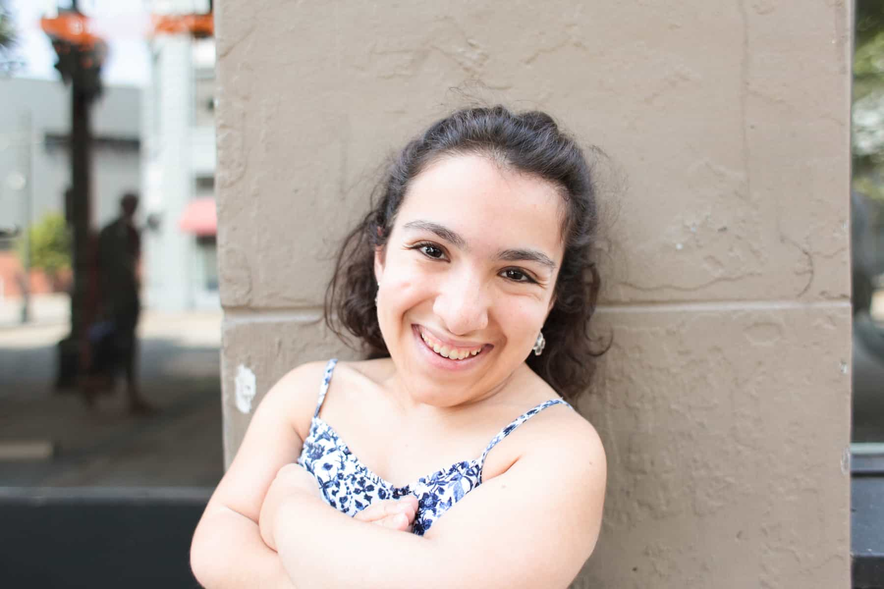 Cuquis smiling, arms crossed with wall in background