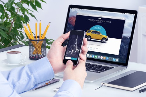 Man uses Uber app on cell phone and laptop