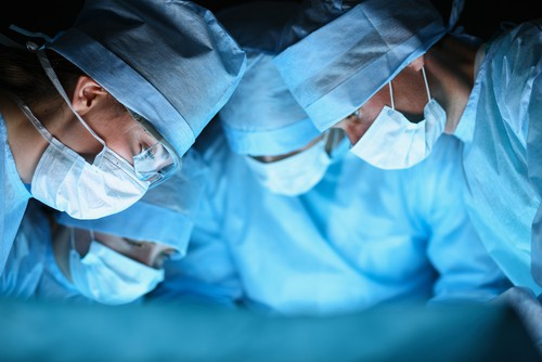 surgeons huddling together during surgery