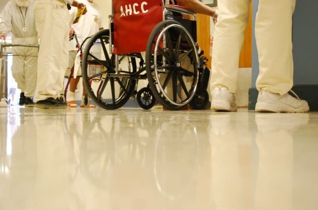 prisoners' feet and the wheels of a wheelchair