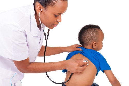 African American doctor examines child