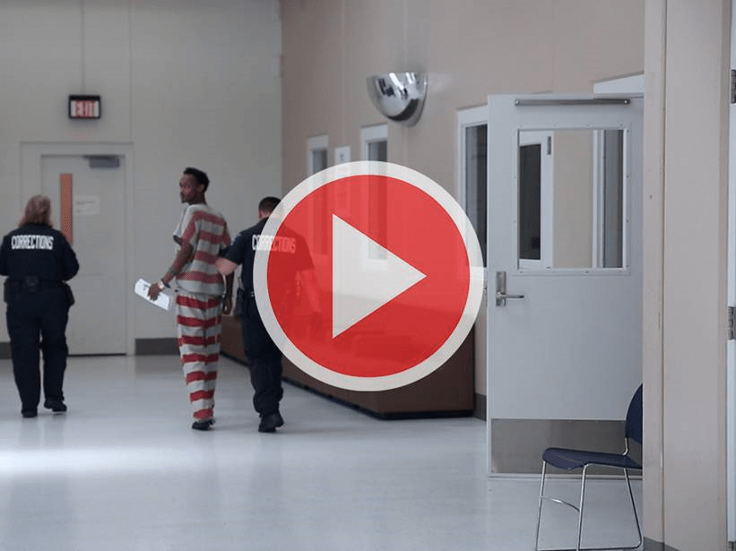 Inmate is led down a jail hall by guards