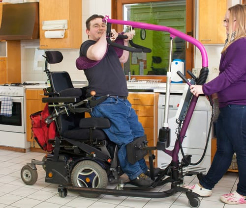Personal Assistant holds assistive lift device as man transfers to a wheelchair