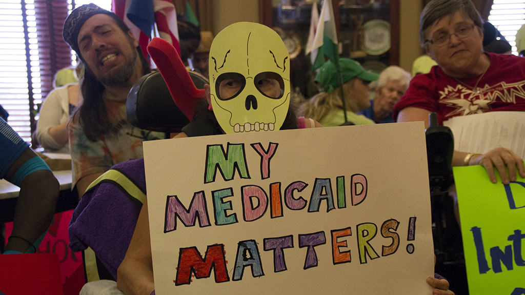 "protestor wearing a skull mask holds sign saying ""My Medicaid Matters"""