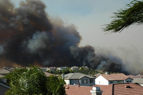 smoke from a wildfire approaching houses