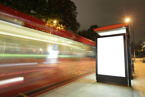 Bus stop shelter at night with vehicles passing at fast speed
