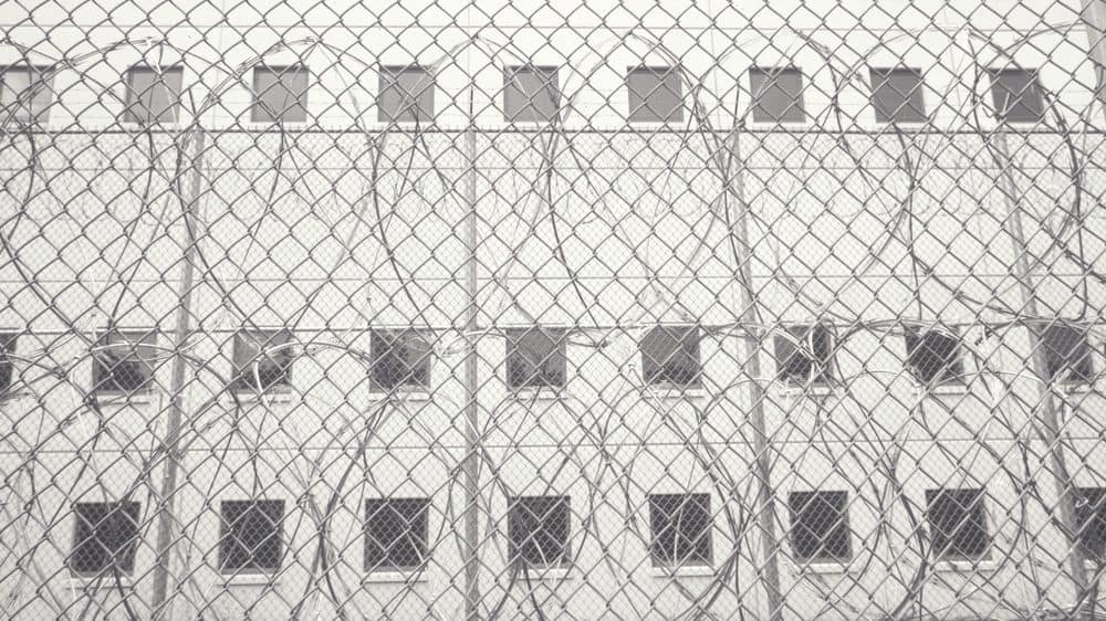 Barbed wire in front of the outside wall of a prison with dark windows