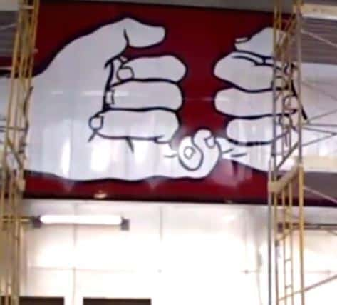 large art of two hands with pinkie fingers linking, with scaffolding in the foreground