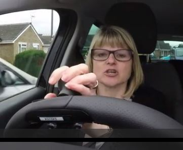 woman using hand controls to drive car