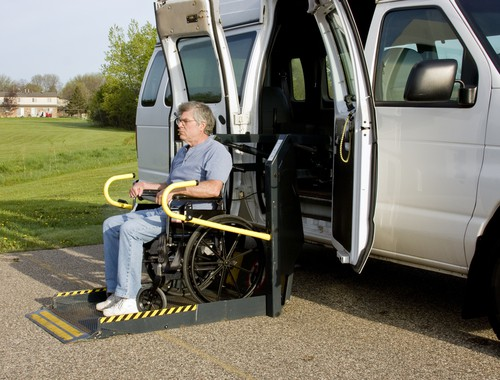 man in wheelchair on an accessible van lift