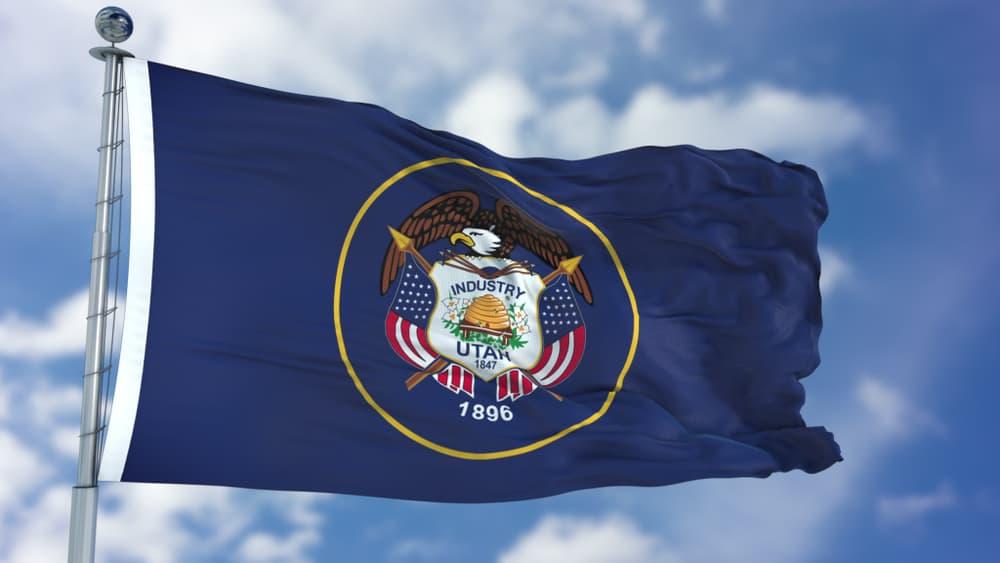 utah flag waving in the wind against a blue sky