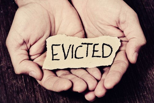 "hands holding a piece of paper with the word ""EVICTED"""