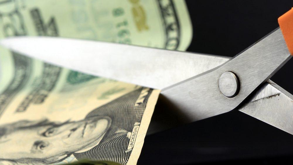 close-up of scissors cutting a twenty dollar bill