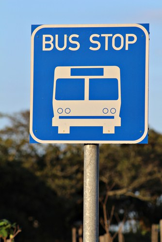 "Blue sign with image of a bus and words ""bus stop"""