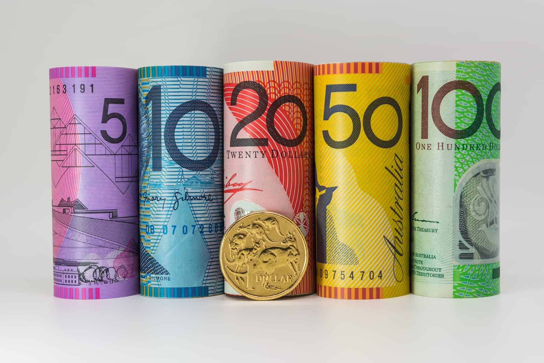 Rolls of Australian paper currency and a 1 Australian Dollar coin