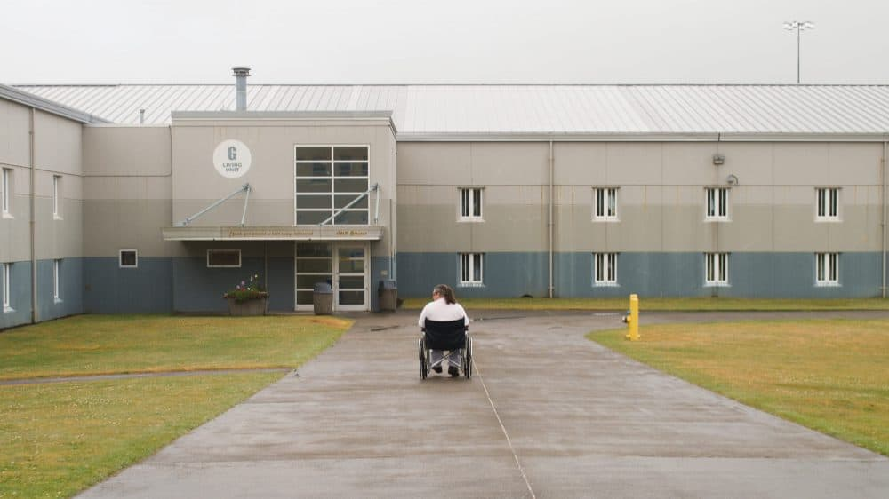 prison yard and building with man in wheelchair rolling away