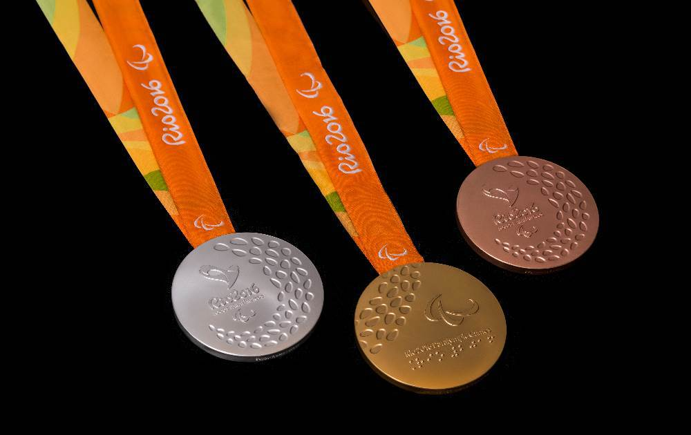 Gold, Silver and Bronze Paralympics medals with orange ribbons