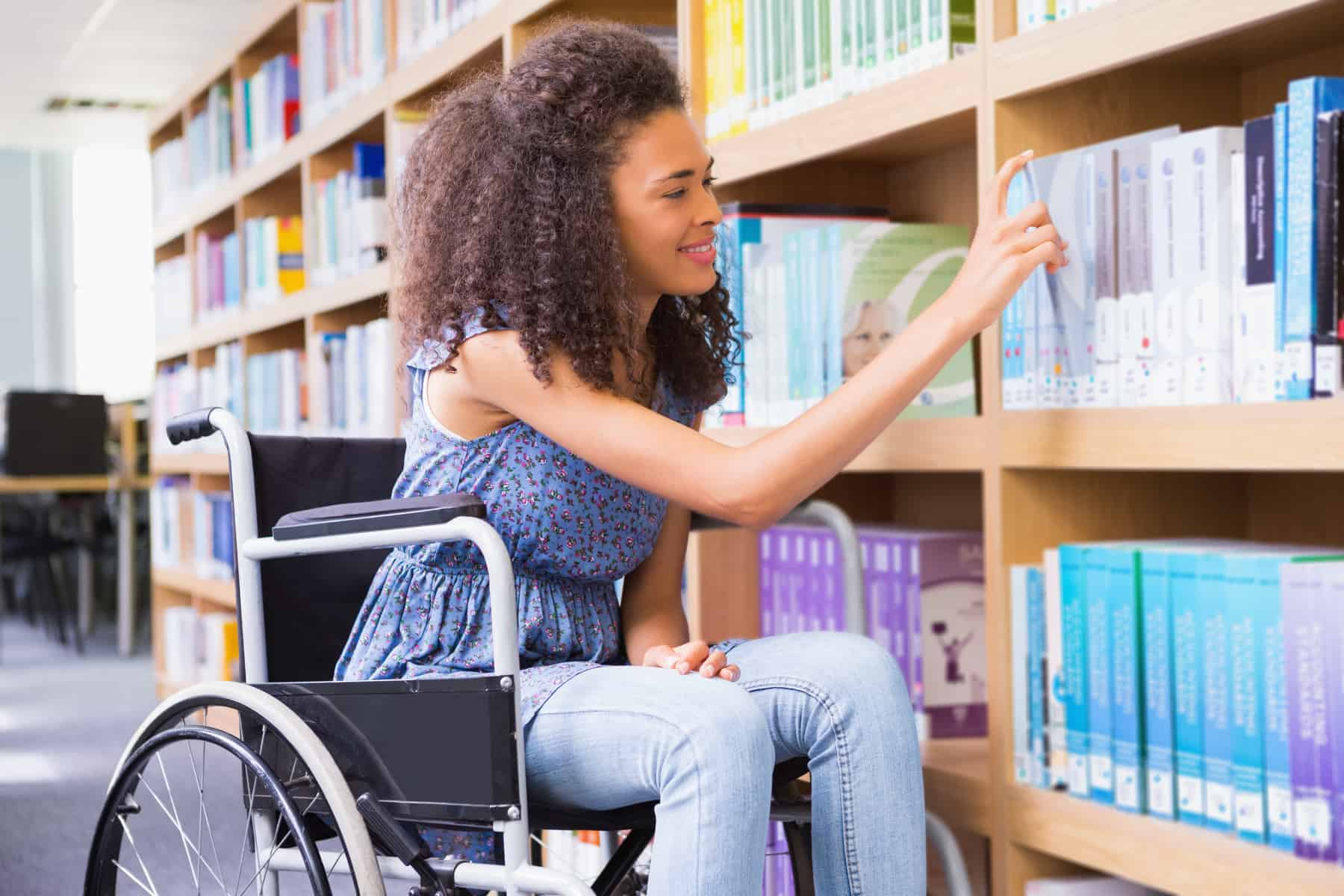young woman in wheelchair selecting a book from a shelf