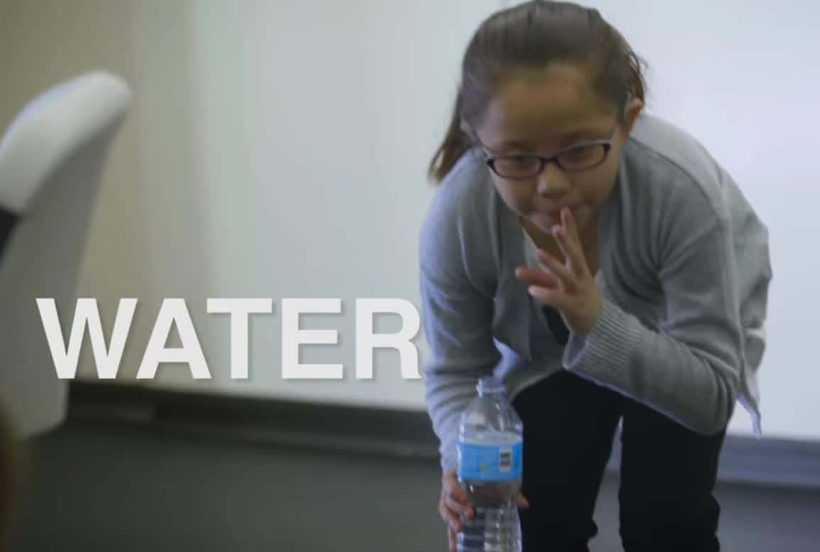 Young girl signing W for water, holding a plastic bottle of water